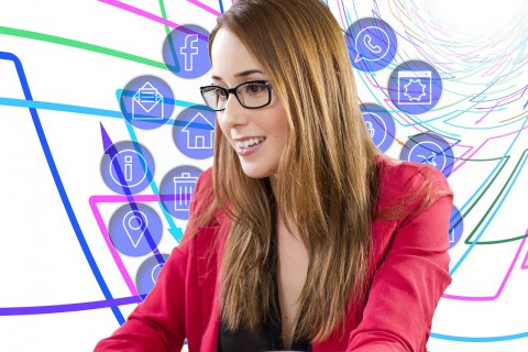 naine istub arvuti taga ja taustal sotsiaalmeedia märgid