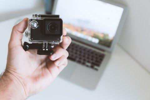 inimese käsi hoiab seikluskaamerat ja läptop arvuti on taustaks